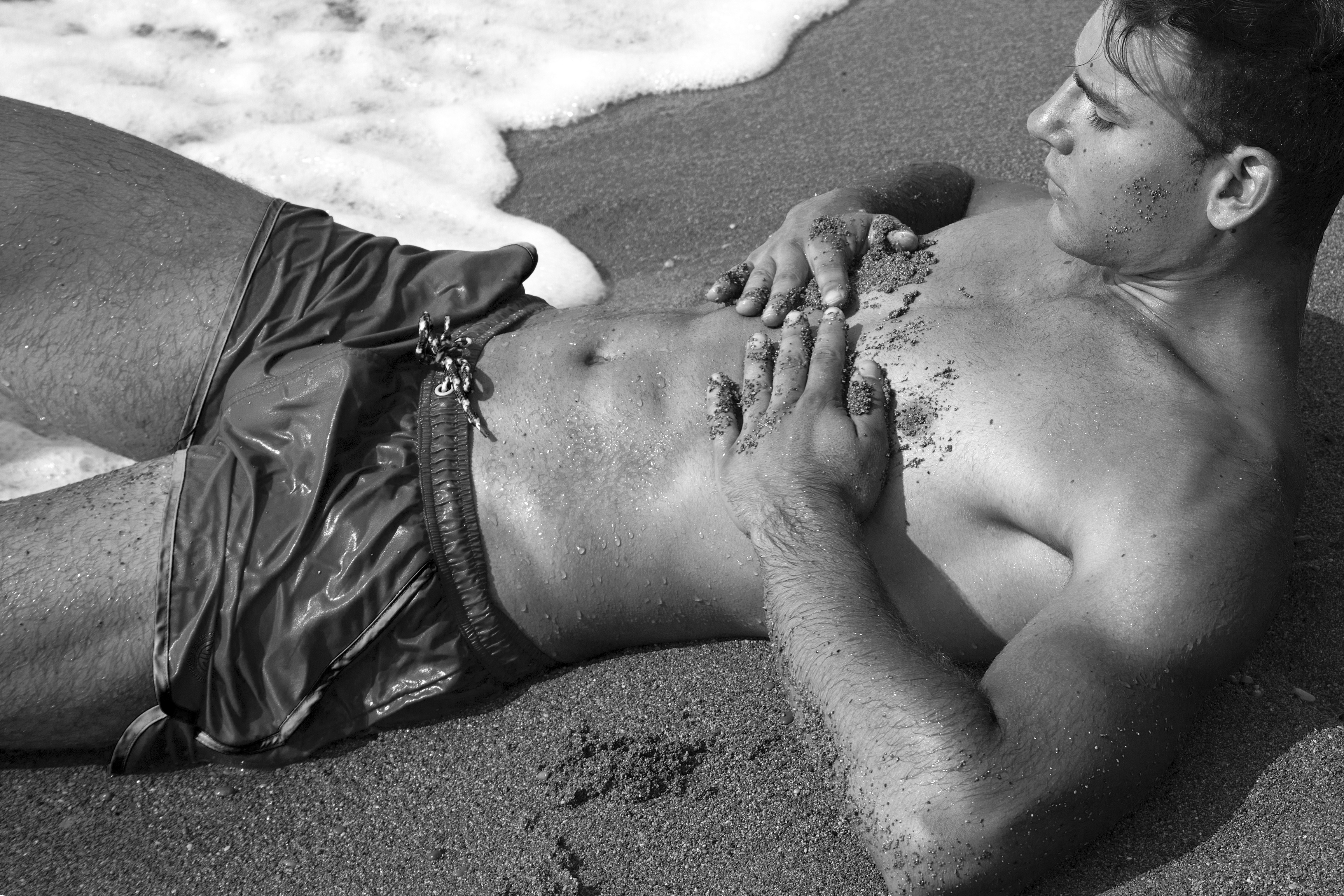 A beautiful beach set with Spanish male model Natán de Segovia showing off candid fit body, swimming in the ocean, connecting to nature, in a sublime photography and video by Jose Martinez.