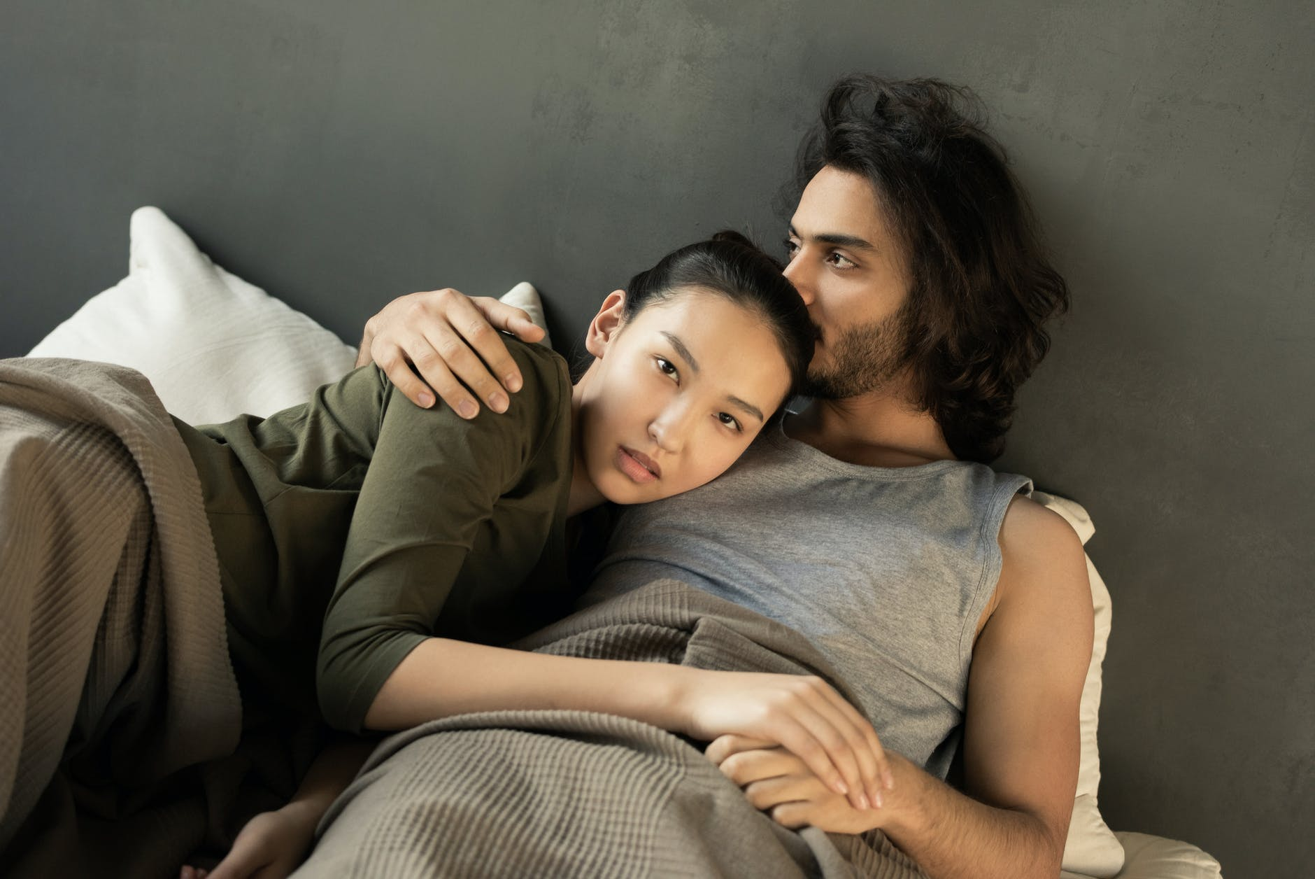woman in green top lying on a man s chest in bed