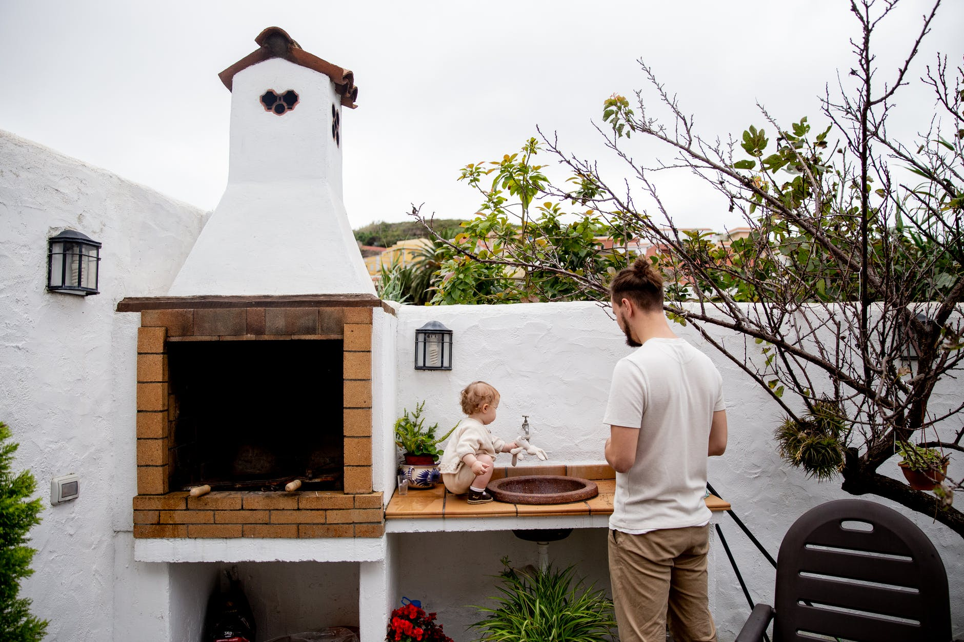 young father with adorable little child near outdoor kitchen